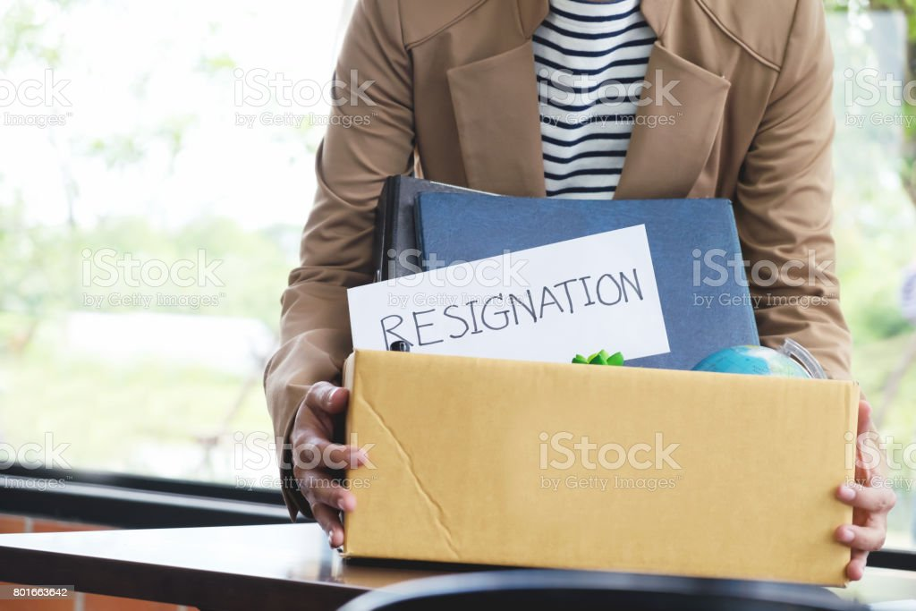 Businesswoman resignation packing up all her personal belongings and files into a brown cardboard box. stock photo