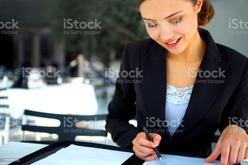 Businesswoman reviewing details in a cafe royalty-free stock photo