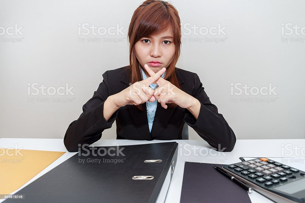 Businesswoman says no with cross fingers on at her office stock photo