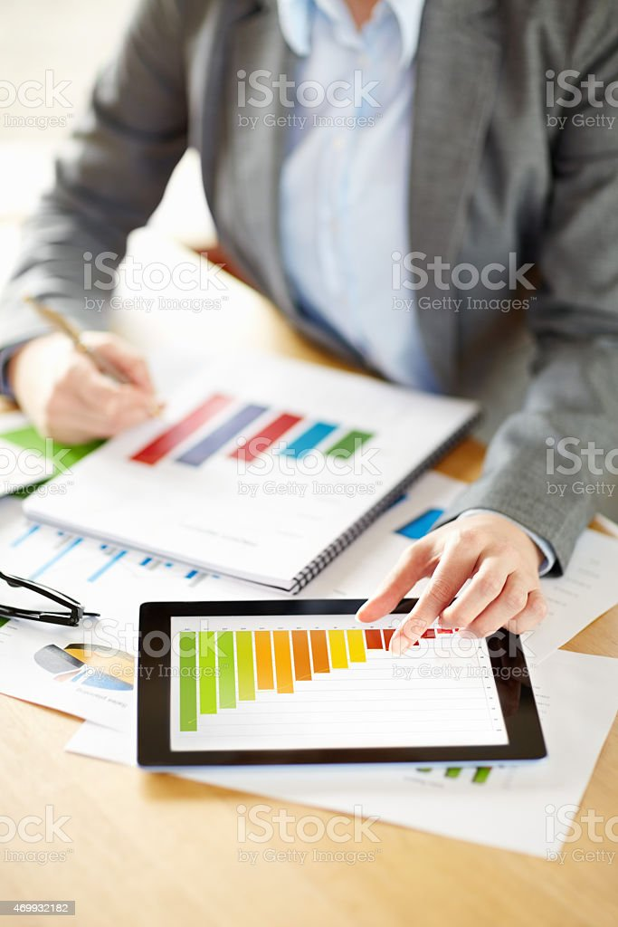 Businesswoman scrutinizing graph at desk stock photo