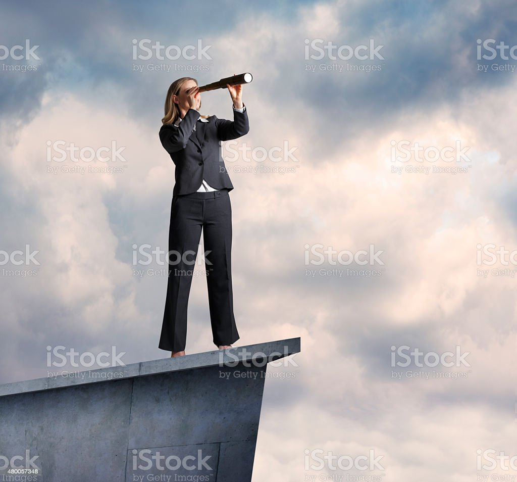 Businesswoman Searching Through Spyglass On Top Of Building stock photo