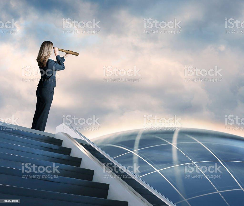 Businesswoman Searching Through Spyglass stock photo
