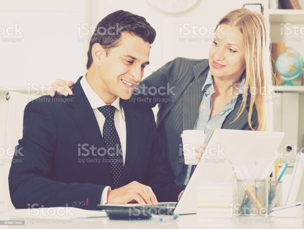 Businesswoman seducing male colleague stock photo