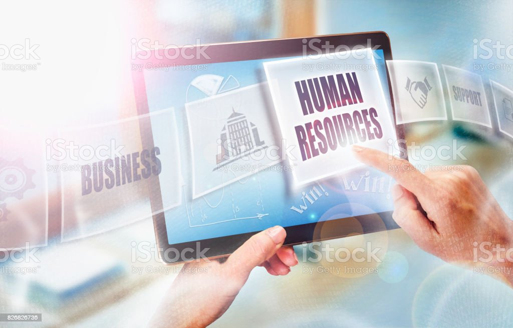 A businesswoman selecting a Human Resources business concept on a futuristic portable computer screen. stock photo