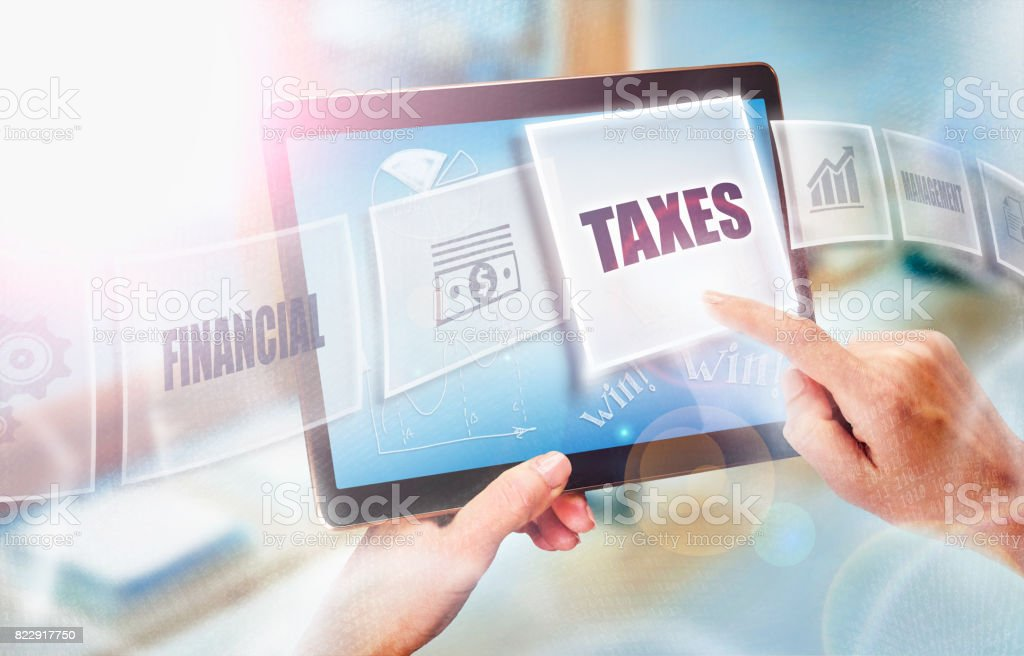 A businesswoman selecting a Taxes business concept on a futuristic portable computer screen. stock photo