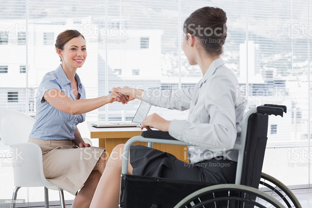 Businesswoman shaking hands with disabled colleague stock photo