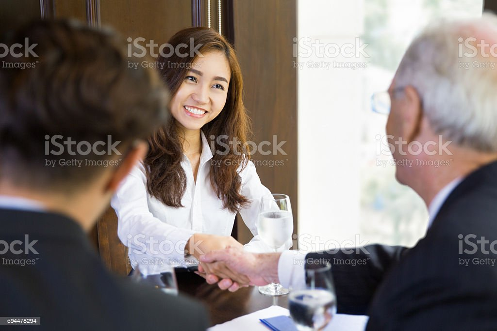 Businesswoman Shaking Hands with Partners stock photo