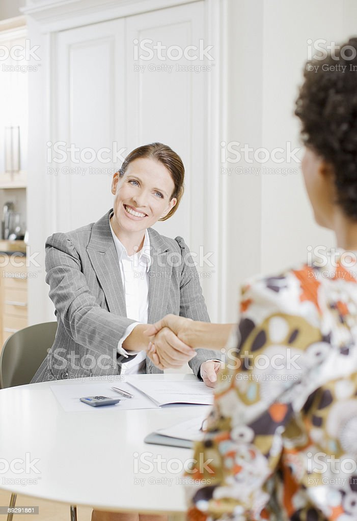 Businesswoman shaking hands with woman stock photo