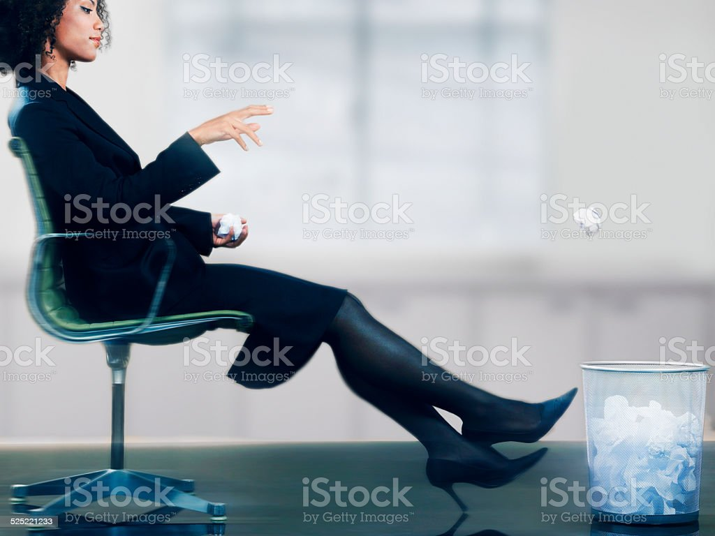 Businesswoman Shooting Wadded Paper into Trash stock photo