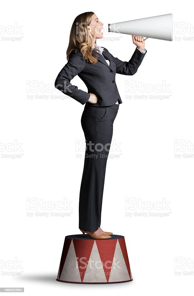 Businesswoman Shouting From Megaphone On Pedestal stock photo
