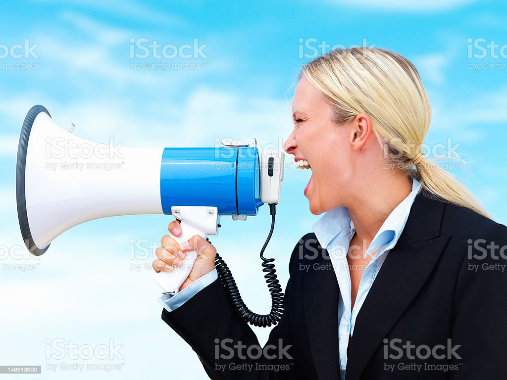 Businesswoman shouting into megaphone against sky royalty-free stock photo
