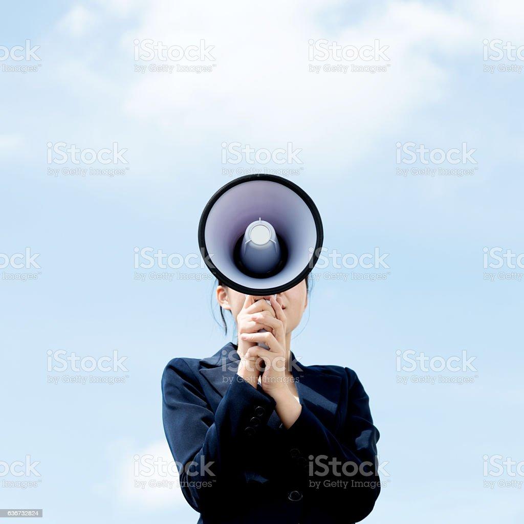 Businesswoman shouting through megaphone stock photo