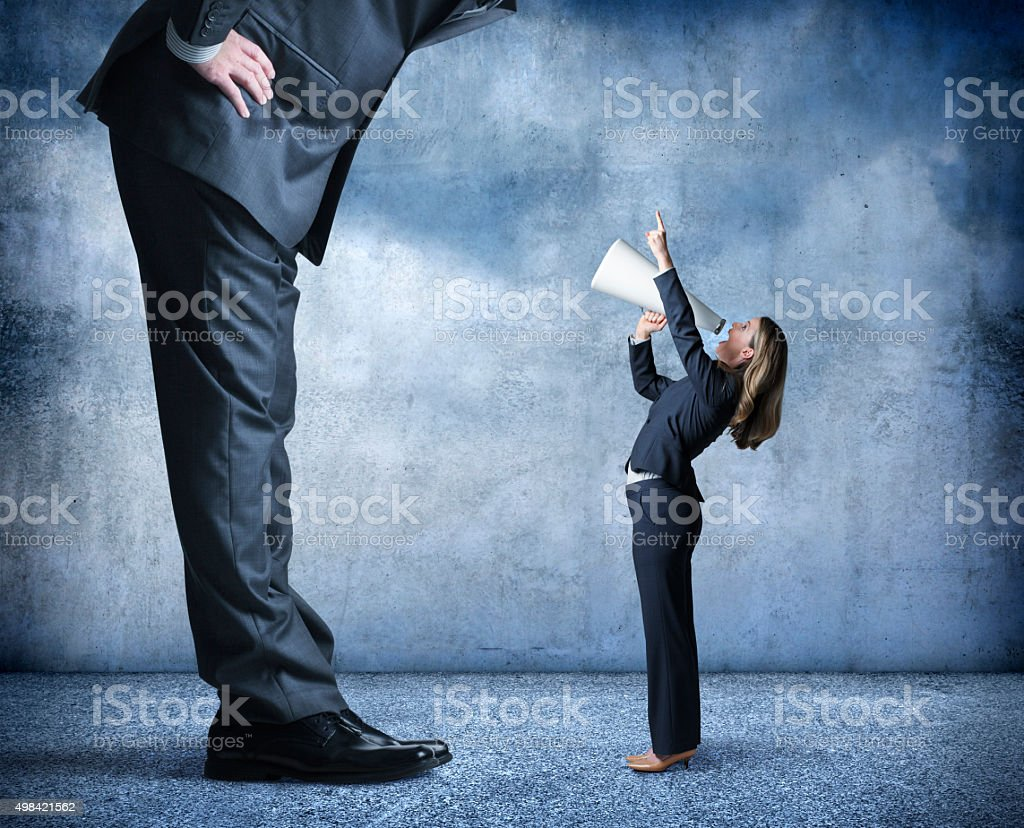 Businesswoman Shouts Through Megaphone Towards Much Larger Businessman stock photo