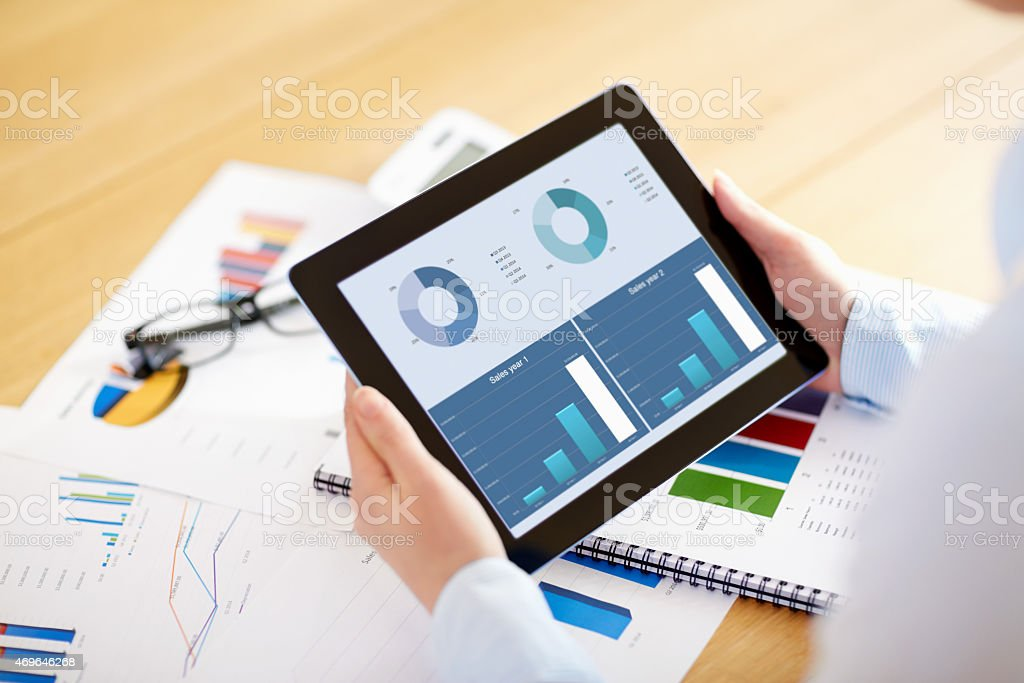Businesswoman showing digital tablet comparing sales stock photo
