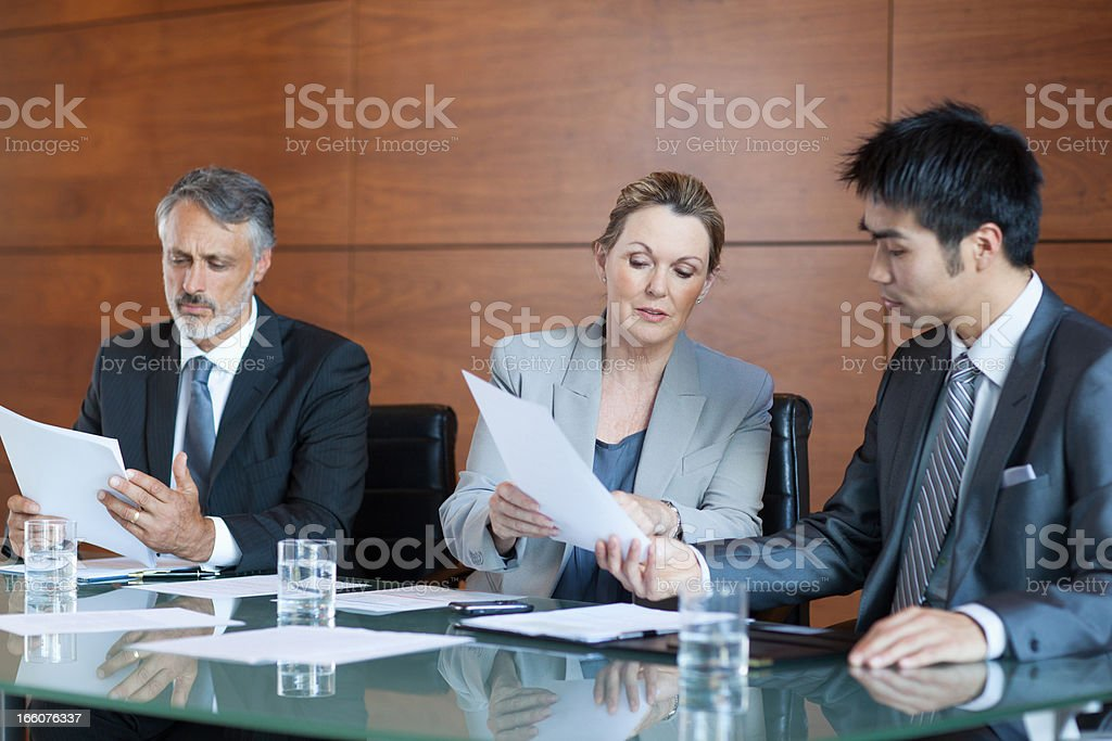 Businesswoman showing paperwork to businessman in meeting royalty-free stock photo