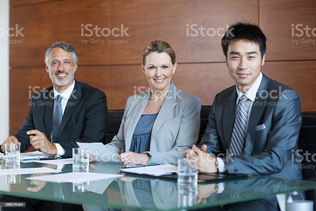 Businesswoman showing paperwork to businessmen in meeting royalty-free stock photo