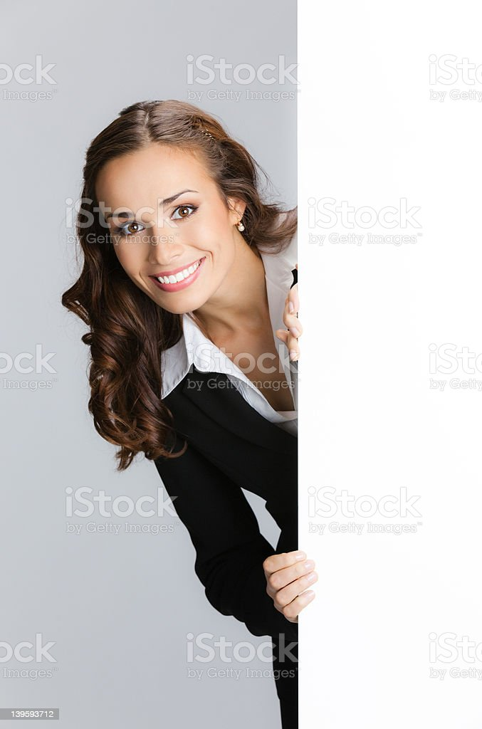 Businesswoman showing signboard, over grey royalty-free stock photo