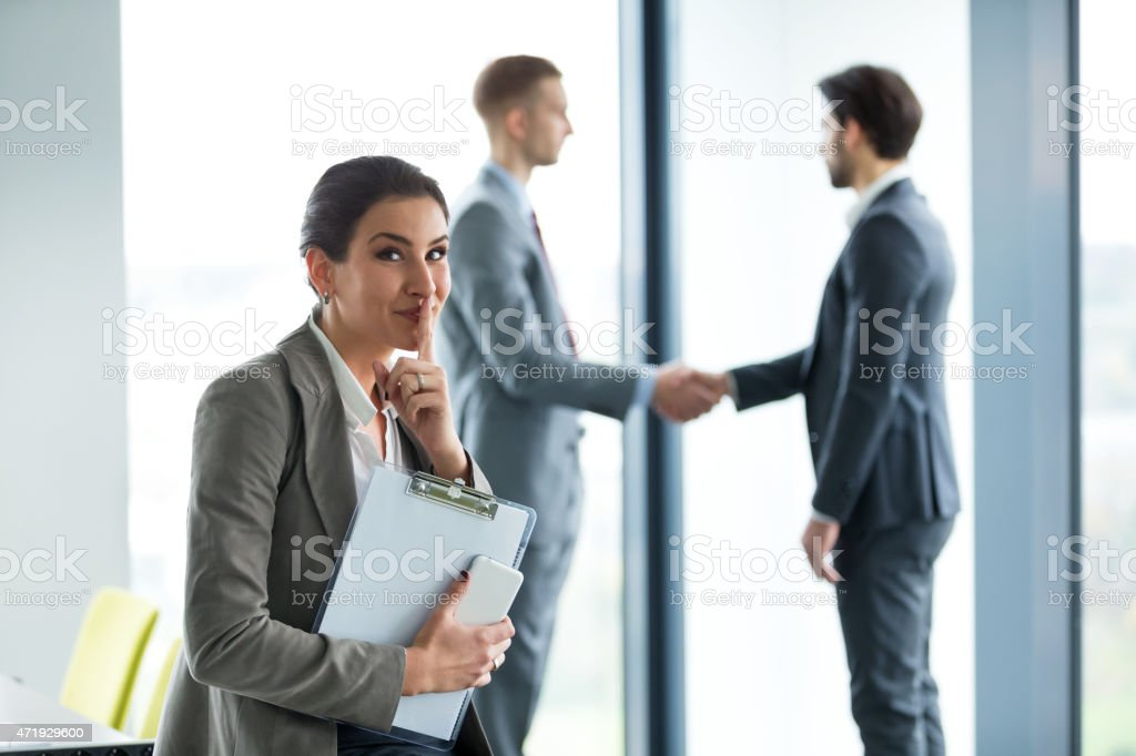 Businesswoman shushes with a smile as two men shake hands  stock photo