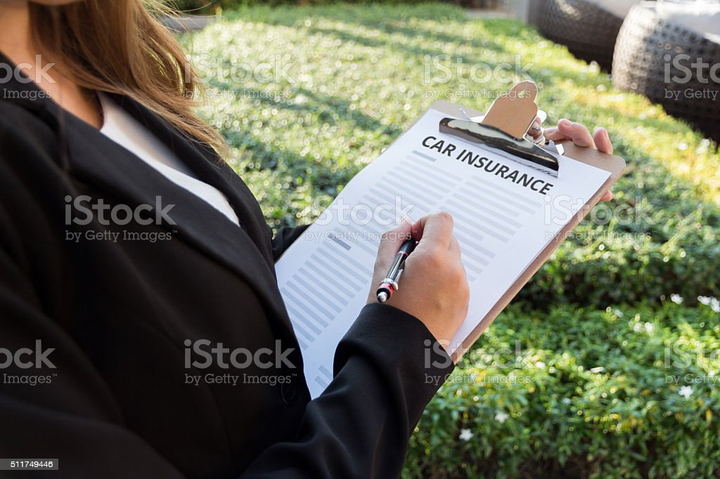 Businesswoman signing a car insurance policy on the street stock photo