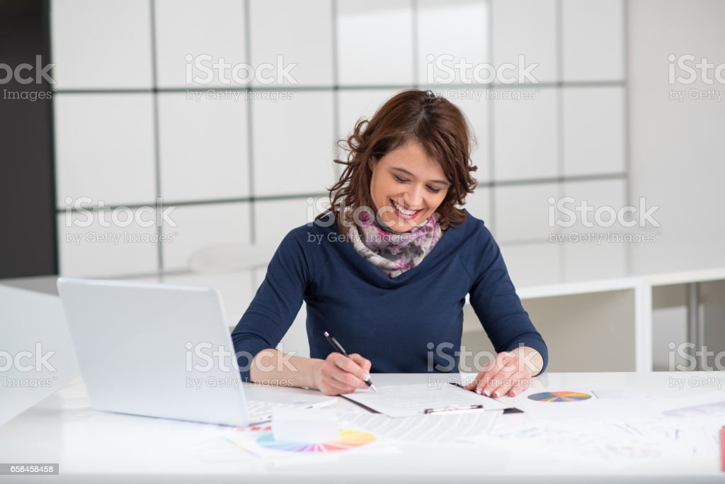 Businesswoman signing contract in office stock photo