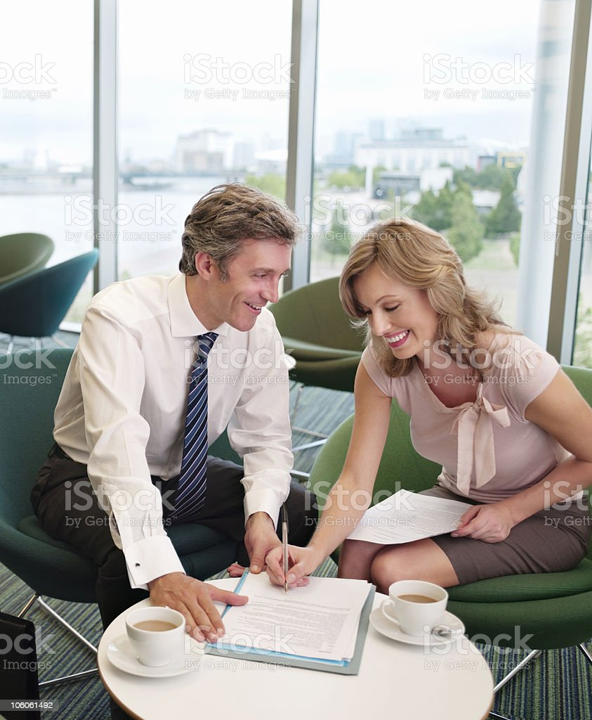 Businesswoman signing document in office canteen stock photo