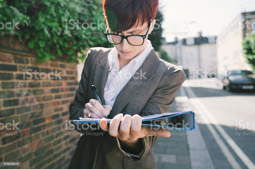 A businesswoman signing documents in a quiet street stock photo