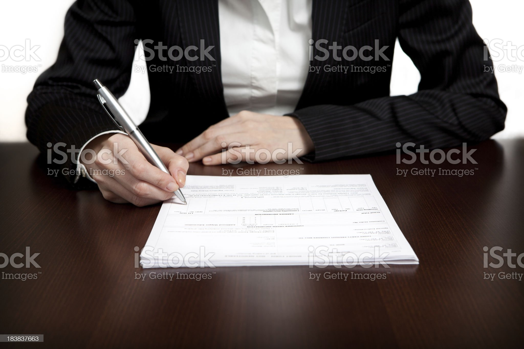 Businesswoman signing documents on a shiny wood table royalty-free stock photo