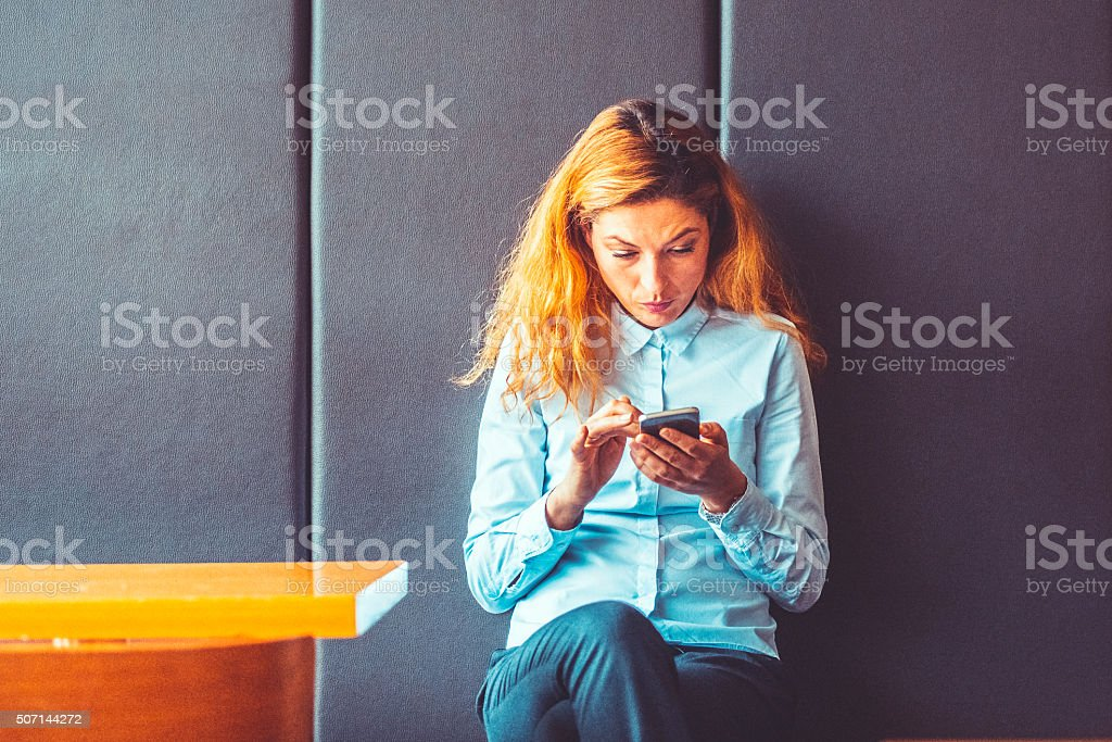 Businesswoman sitting alone in cafe, text messaging stock photo