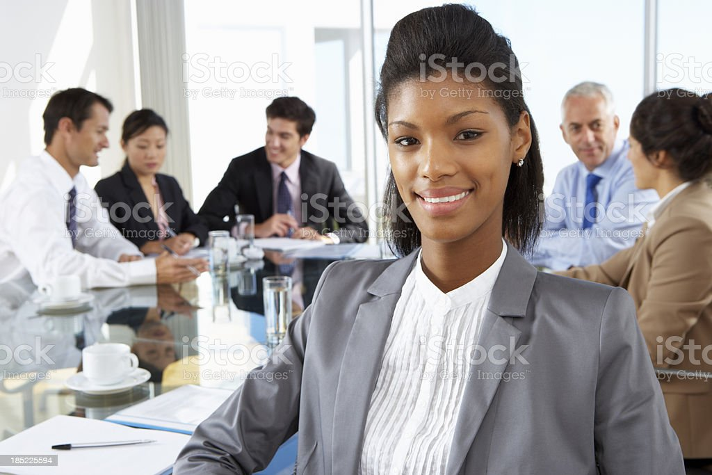 Businesswoman Sitting Around Boardroom Table royalty-free stock photo