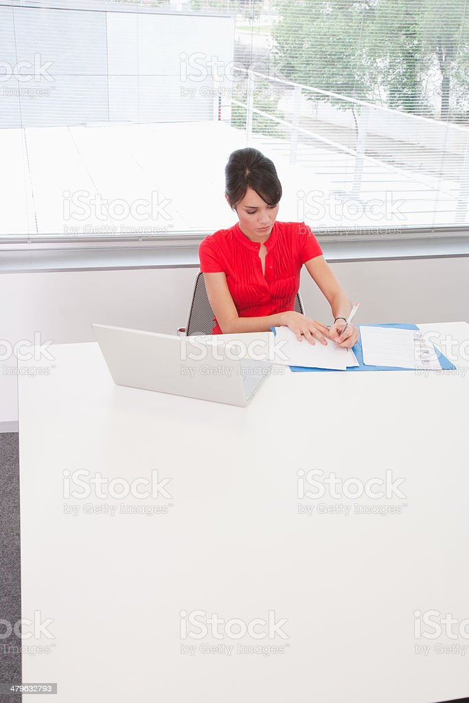 Businesswoman sitting at conference table stock photo