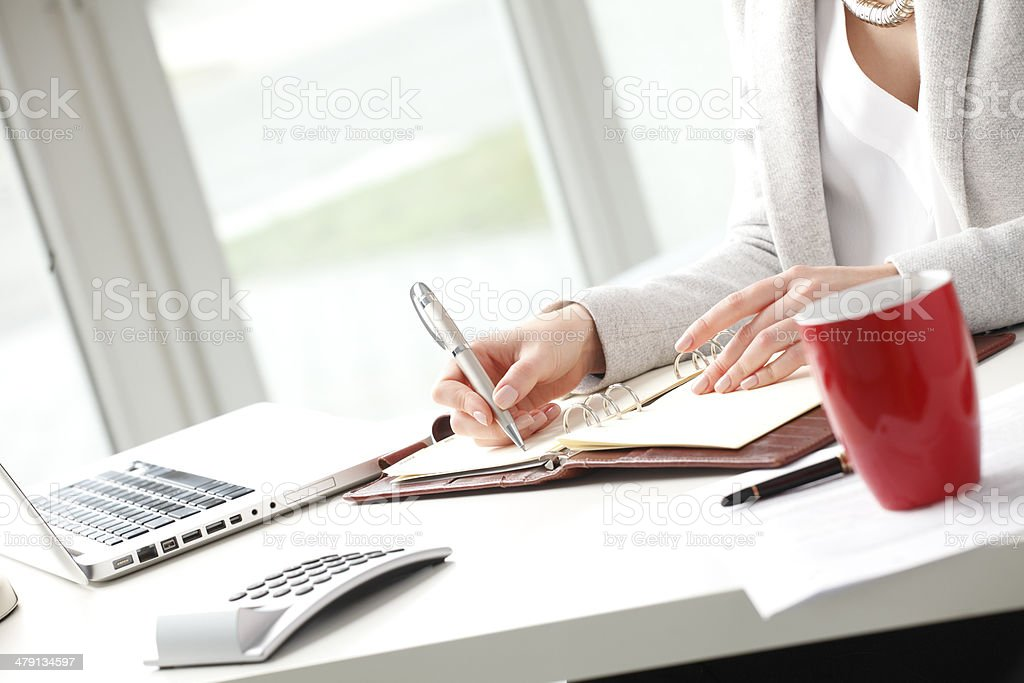 Businesswoman sitting at desk and makes a note in office. stock photo