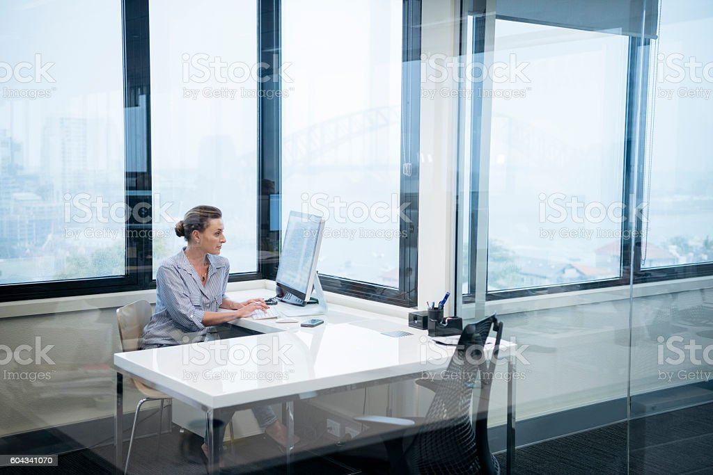 Businesswoman sitting at desk behind glass in modern office stock photo