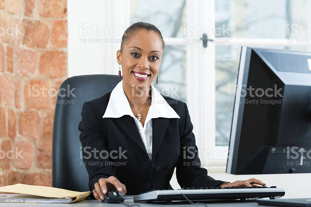 Businesswoman sitting at desk working on computer stock photo