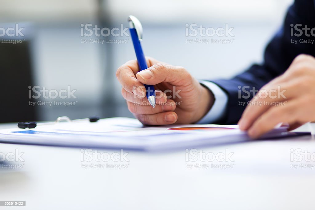 Businesswoman sitting at office desk signing a contract stock photo