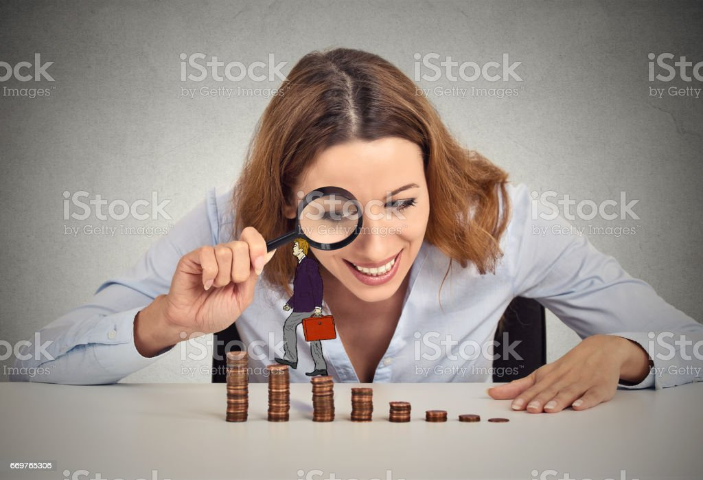 Businesswoman sitting at office table looking at corporate employee walking up coin stack ladder. stock photo