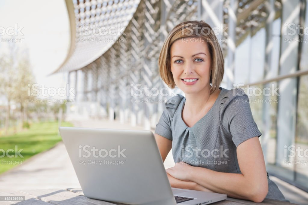 Businesswoman Sitting at Table With a Laptop stock photo