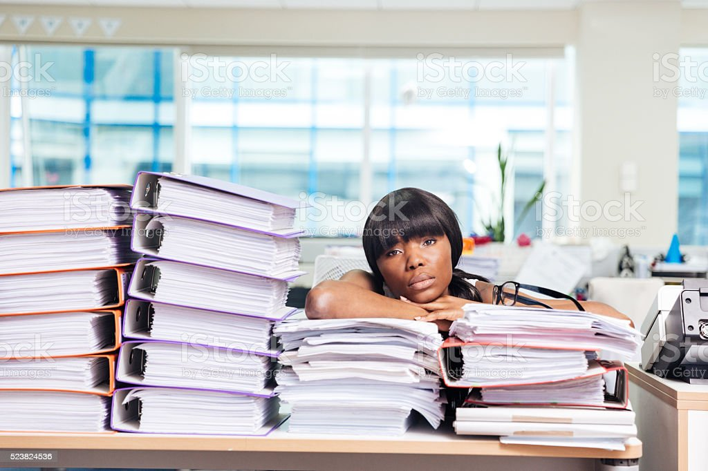 Businesswoman sitting at the table with many work in office stock photo
