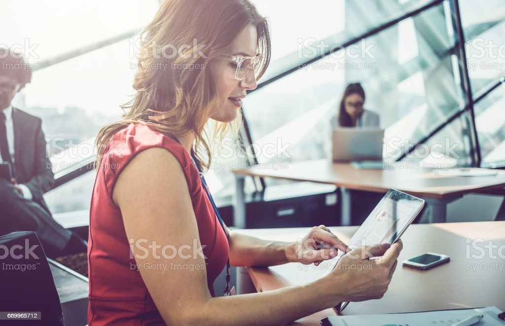 Businesswoman Sitting Behind a Desk and Using Digital tablet stock photo