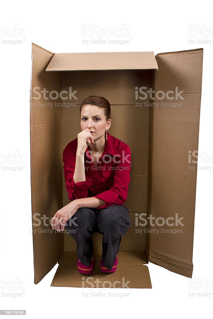 Businesswoman Sitting in a Box Feeling Boxed In royalty-free stock photo