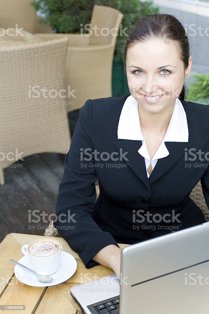 Businesswoman sitting in restaurant with laptop on table royalty-free stock photo