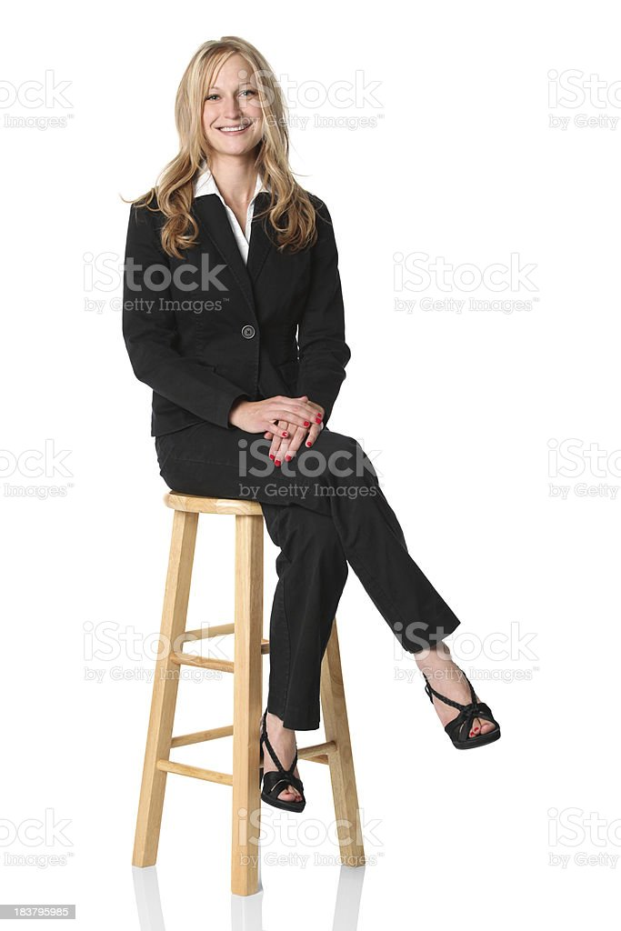 Businesswoman sitting on a high stool stock photo