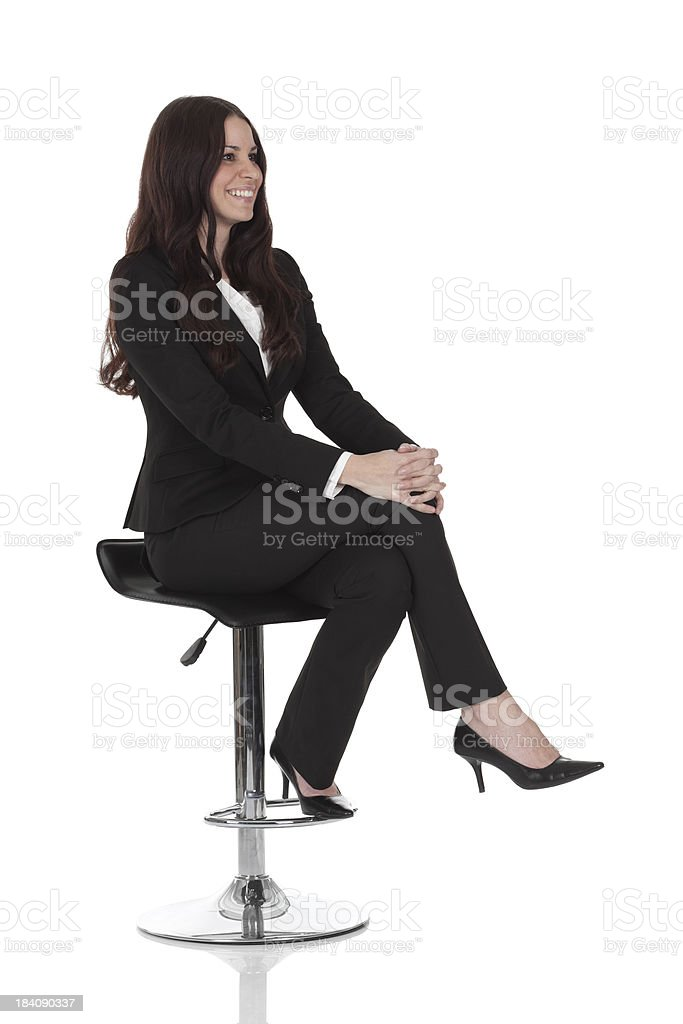 Businesswoman sitting on a stool stock photo