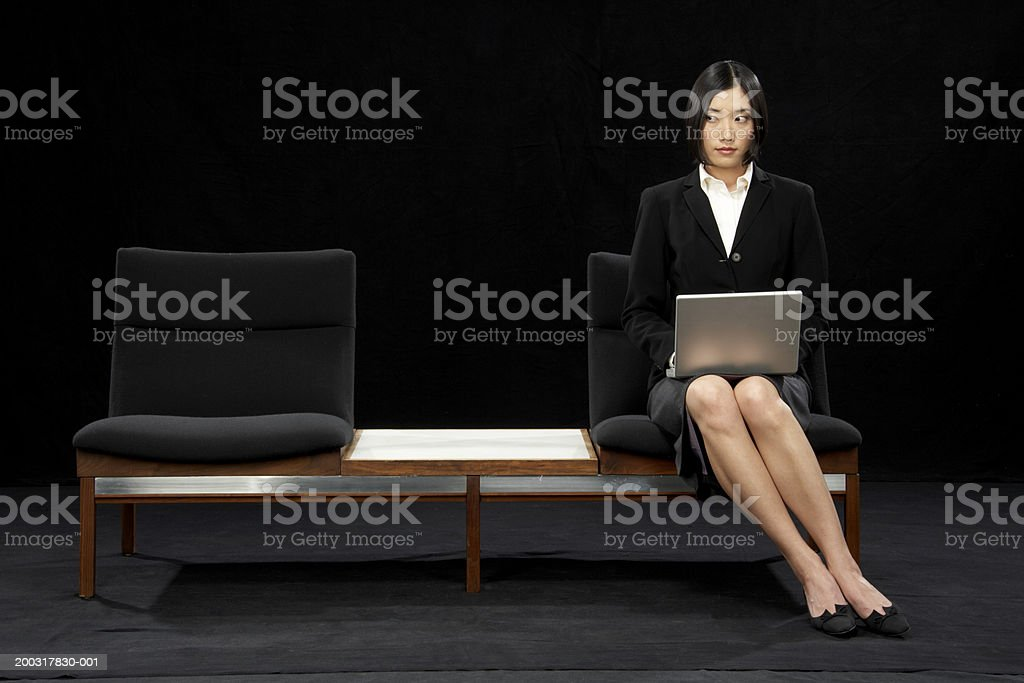 Businesswoman sitting on bench using laptop, looking to one side stock photo