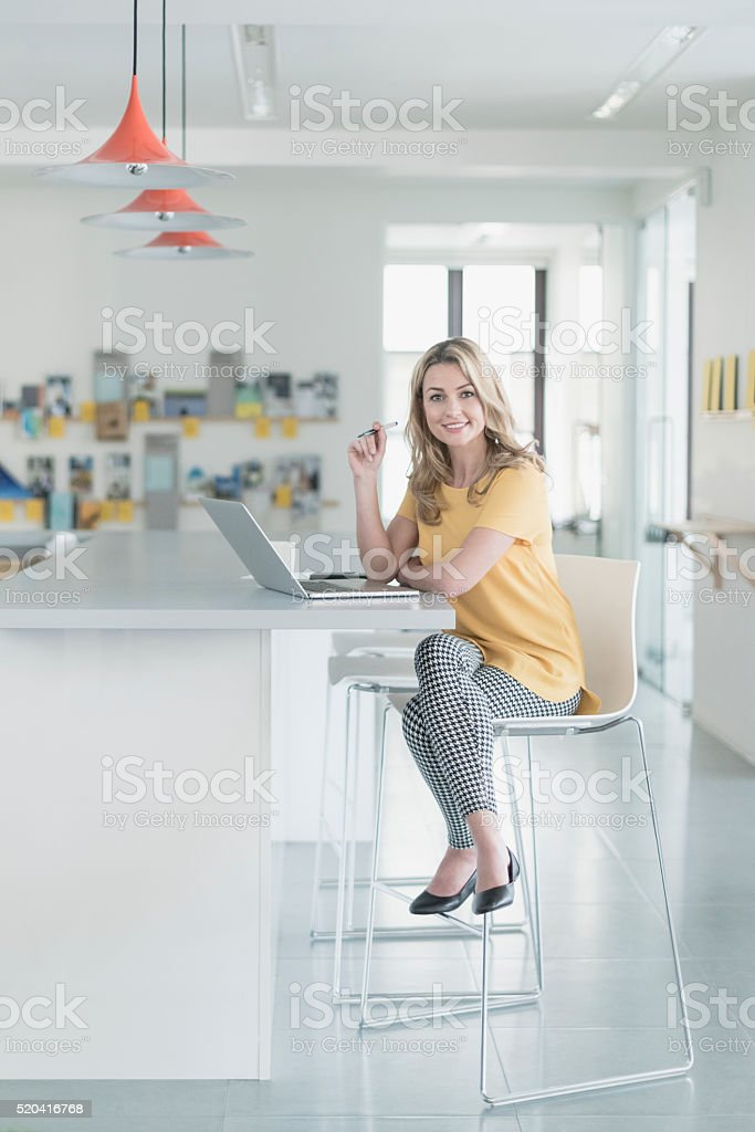 Businesswoman sitting on chair in office with laptop, smiling stock photo