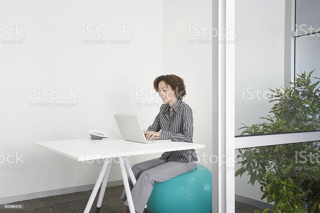 Businesswoman sitting on exercise ball in office royalty-free stock photo