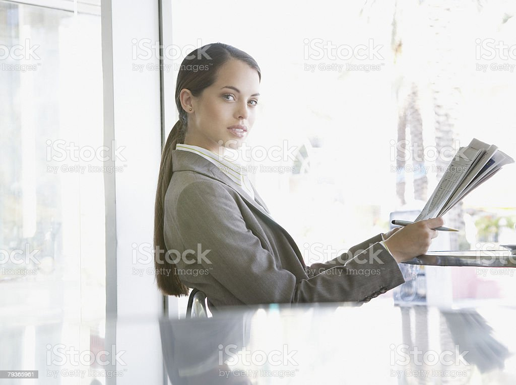 Businesswoman sitting on outdoor patio with newspaper royalty-free stock photo