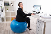 Businesswoman Sitting On Pilates Ball Using Computer