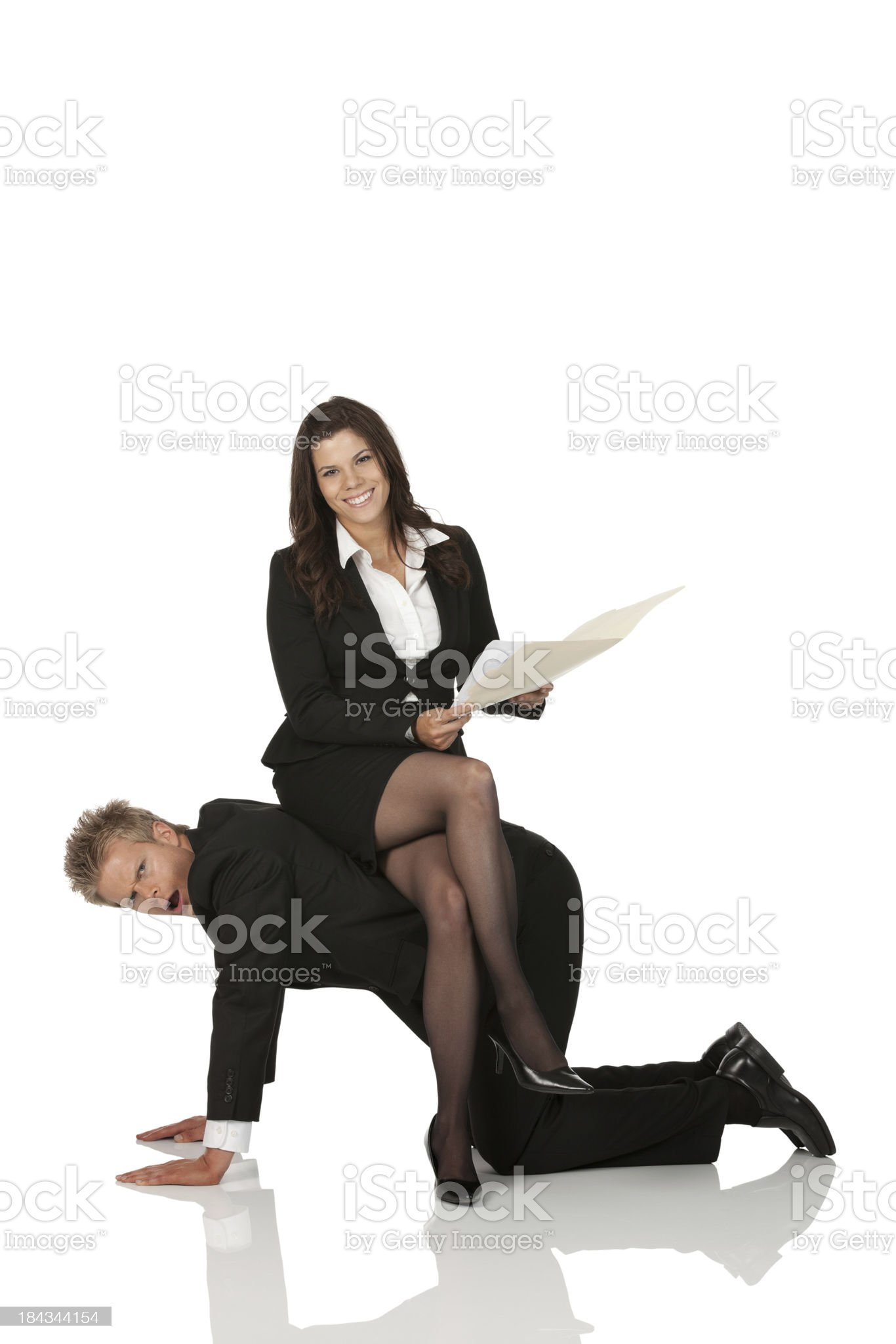 Businesswoman sitting on the back of a man royalty-free stock photo