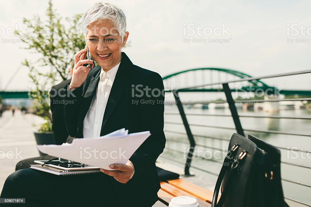 Businesswoman Sitting On The Bench And Talking On Her Phone. stock photo