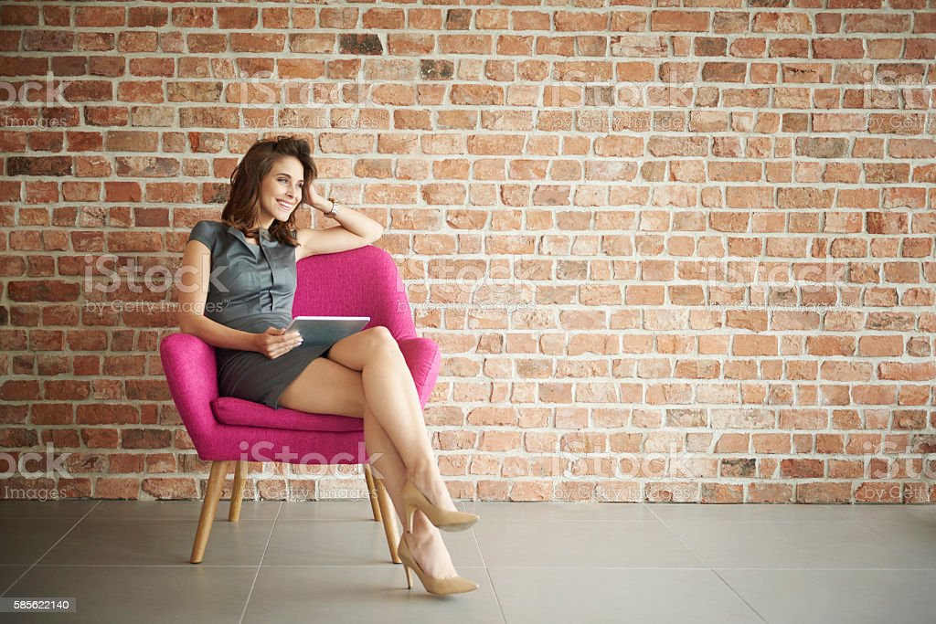Businesswoman sitting on the pink armchair stock photo